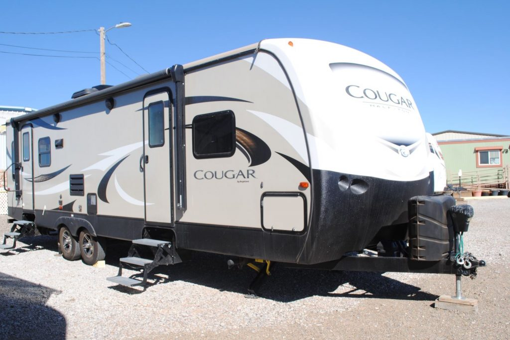 Exterior Front view with hitch and right side of camper, two doors with steps extended, two windows,