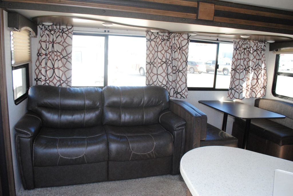 Leather loveseat, table with two bench seats, windows, partial view of counter top