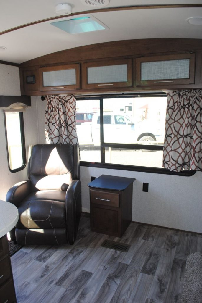 Large window, overhead storage, reclining chair and side table with storage