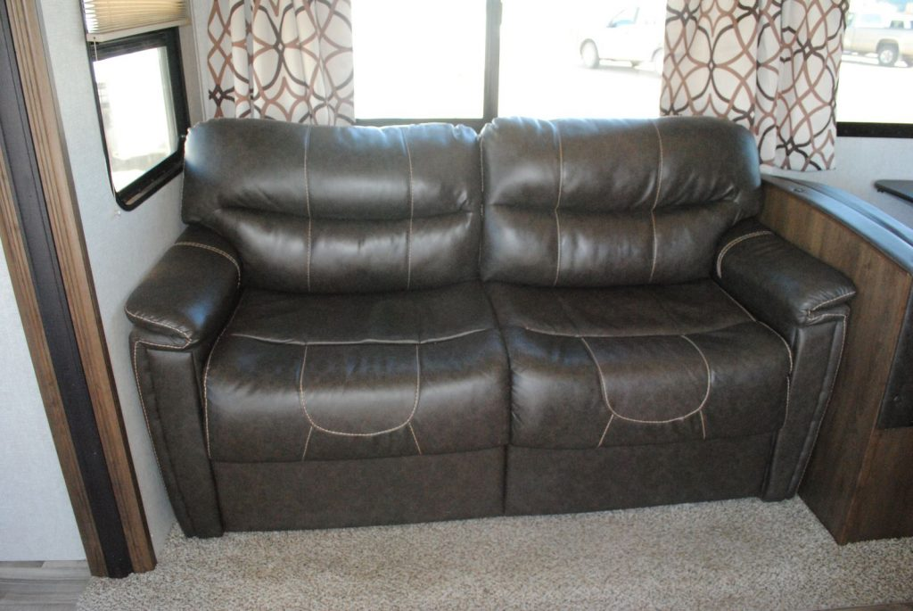 Close up view of leather love seat and windows, carpet under loveseat