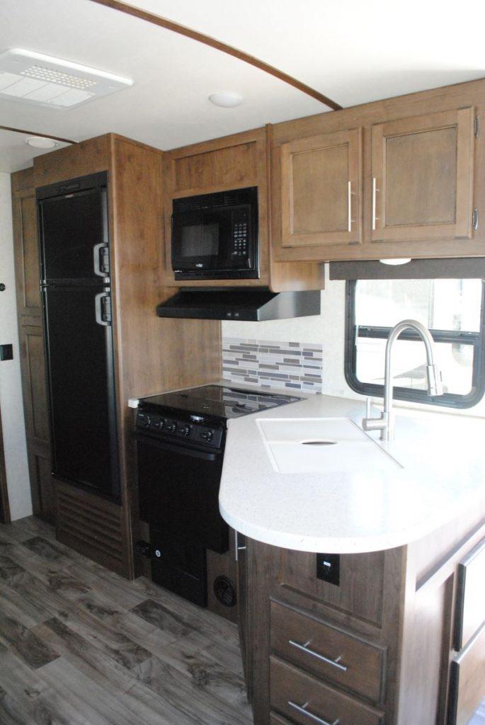 Refrigerator, microwave, range hood, range, sink, window, counter top, cabinets and veneer flooring