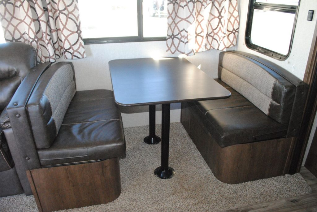 table in the middle of two bench seats, carpet under table and seats