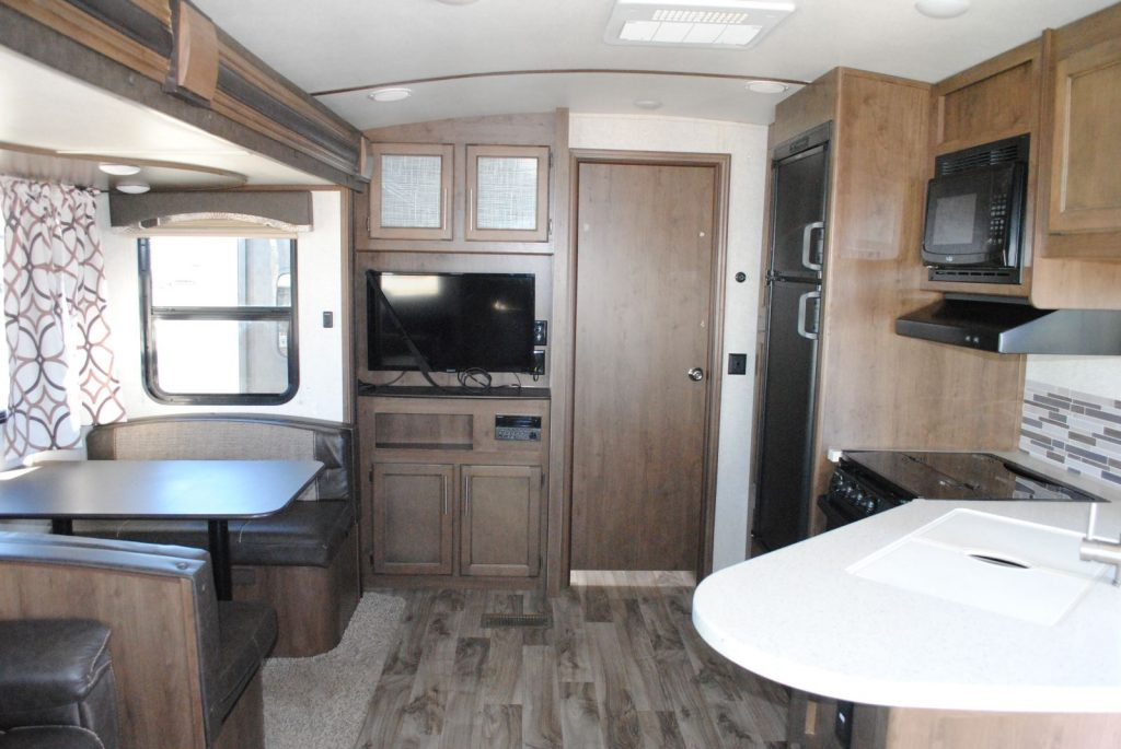 Long view of table bench seating, TV, interior door, refrigerator, microwave, stove, hood, sink and counter