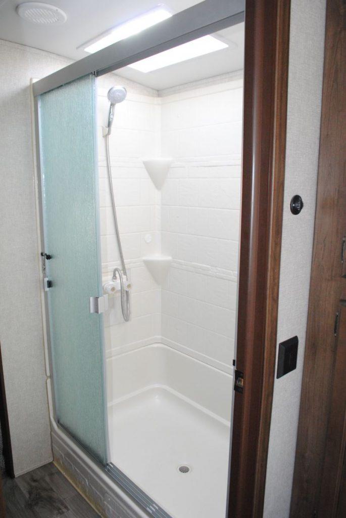Shower enclosure, two sliding doors, skylight above shower