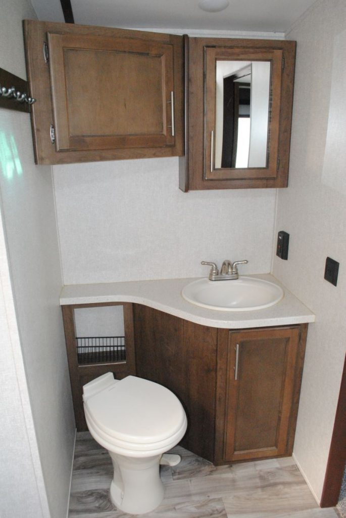 Restroom view, toilet, sink and cabinets, mirror above the sink