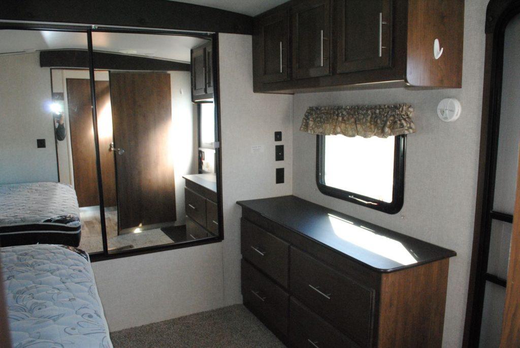 Mirrored closet doors, clothes storage drawers, foot of mattress, carpet floor, small window