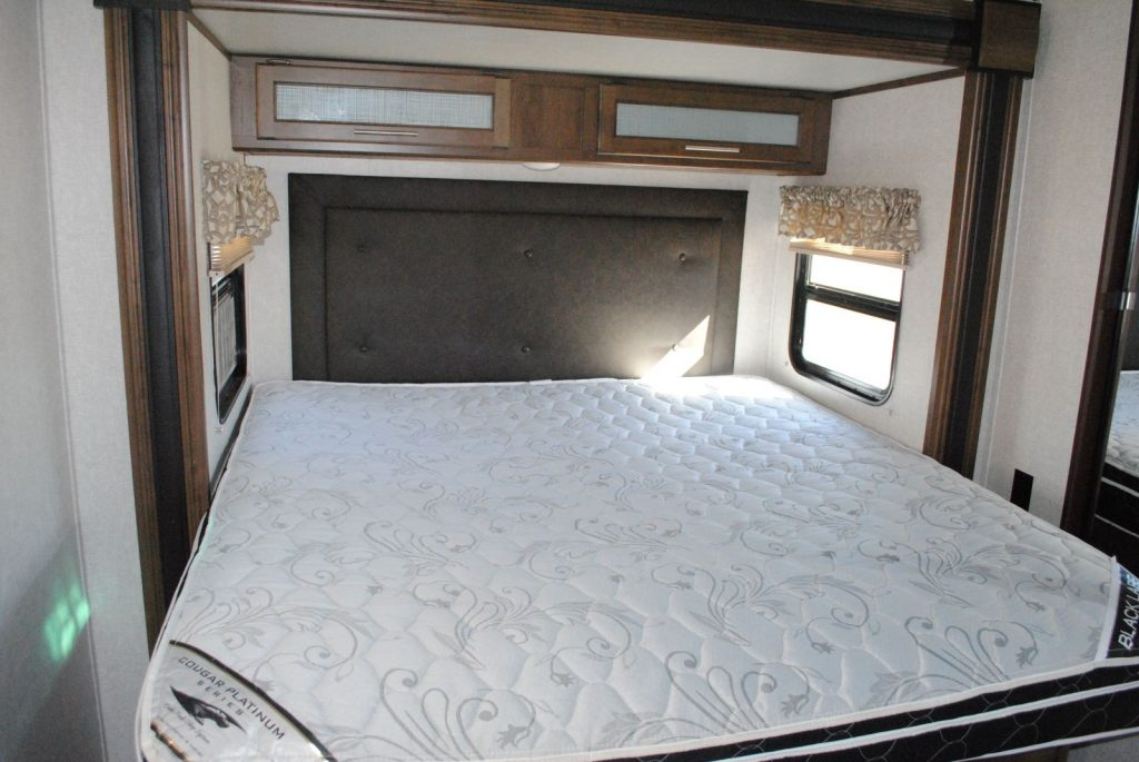 At foot of mattress, mattress goes from wall to wall, no walk around space, window on each side of bed, small overhead cabinets