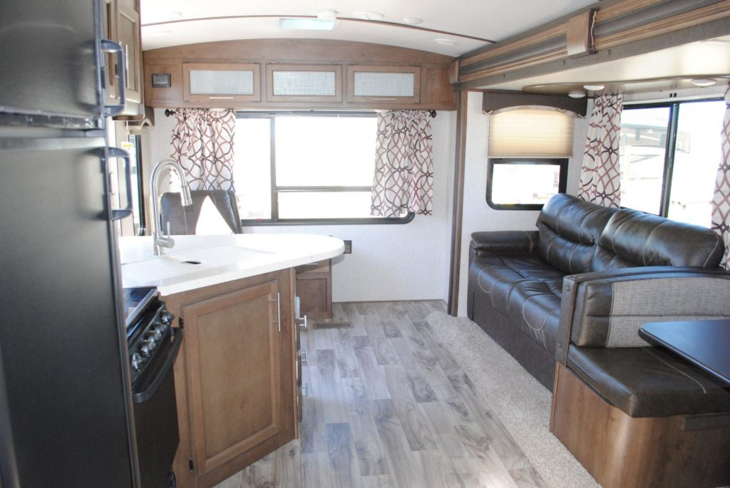 View of kitchen and sitting area, large window on end of trailer, one smaller window and large window on pull out section.