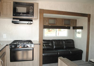 Stove, range hood, microwave. Cabinet storage. Sofa with overhead storage and windows.