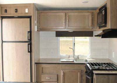 Kitchen view. Refrigerator, sink, window. Storage cabinets. Stove and mircorwave.