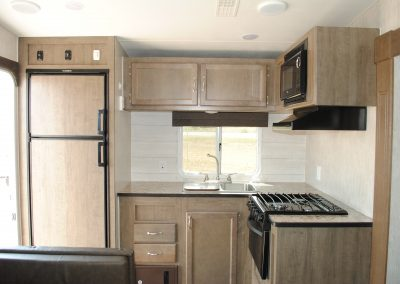 Refrigerator, double sink, stove, oven, microwave. Cabinet storage.