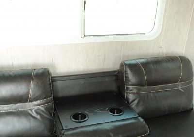 Close up of sofa. Middle seat back pulls down with a drink caddy.