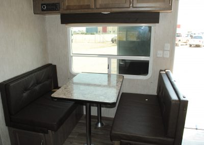 Table, bench seating. Large window and overhead storage.