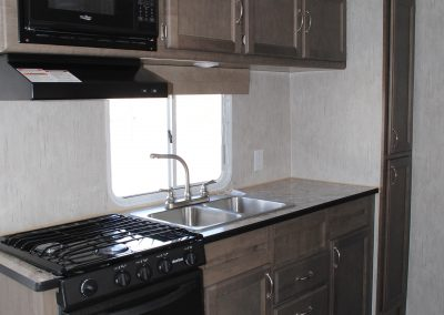 Stove, stove hood and microwave. Sink and cabinet storage.