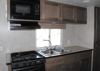 Stove, stove hood, microwave and sink. Counter top and storage cabinets.