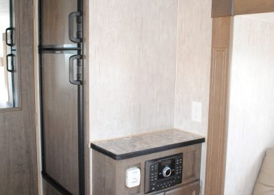 Refrigerator, cabinet with storage. Partial view of sofa.