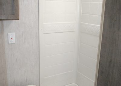 Toilet and shower stall, shower curtain rod.