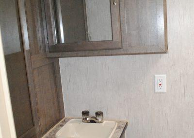 Bathroom sink. Under sink cabinet. Over head cabinet with mirror on door.