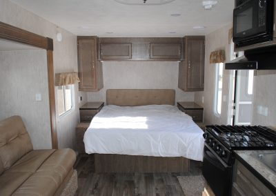 Long view of sofa, stove, microwave, stove hood, partial sink. Bed walking space on both sides of bed. Side bed storage and overhead storage.