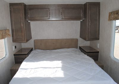Close up view of bed and storage cabinets.