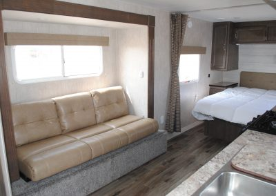 Sofa with sliding window, partial view of bed and kitchen sink.