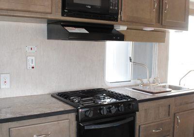 Stove, range hood, microwave and sink. Cabinet storage.