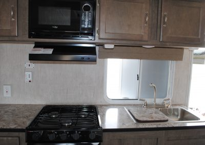 Stove, range hood and microwave. Sink with small window. Cabinet storage. Counter top.