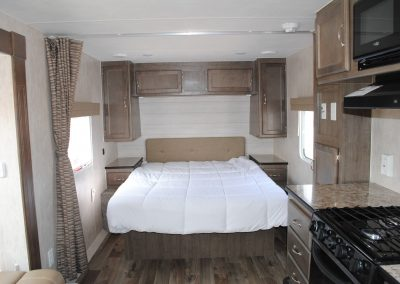 Partial view of stove, range hood and microwave. View of bed, walking space on both sides. Storage on sides and above bed.