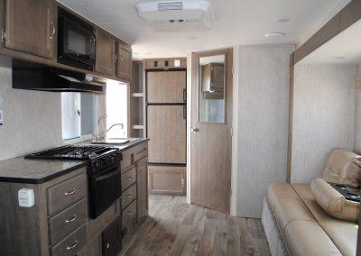 Long view of stove, hood and microwav. Sofa. Refrigerator and interior door.