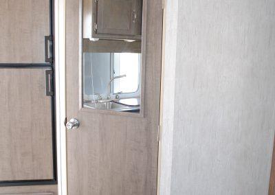 Partial view of refrigerator. Interior door with mirror.
