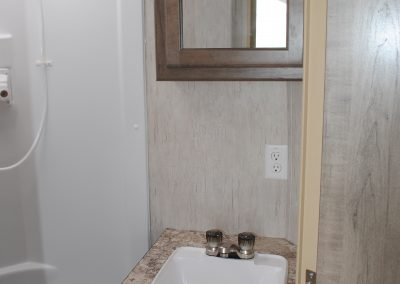 Sink and medicine cabinet with mirror. Partial view of shower.