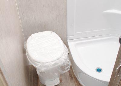Corner toilet next to shower.
