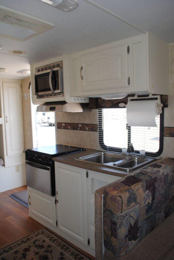 Kitchen sink, window, stove, stove hood, microwave, cabinet storage and front door.