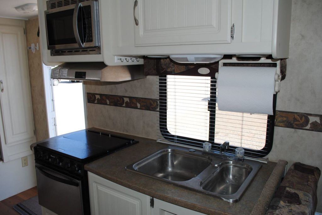 Close up of sink, window, stove and microwave. Cabinet storage.