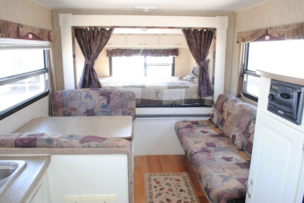 Long view of table and bench seating, sofa and bed. Three windows.