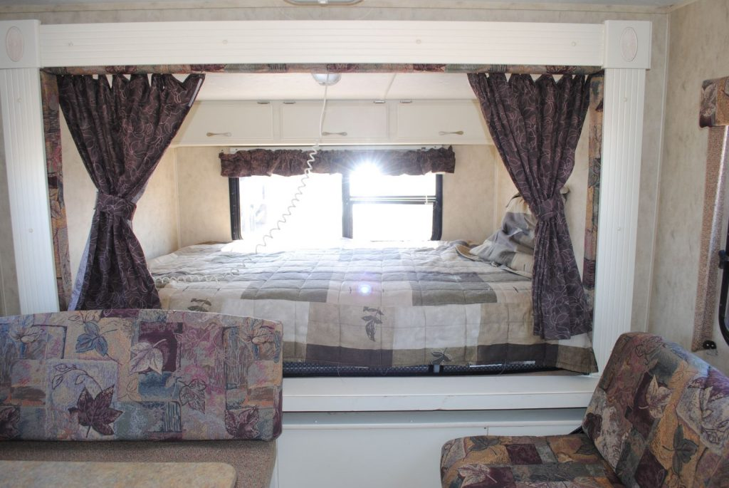 Close up view of bed and window. Side privacy curtains.