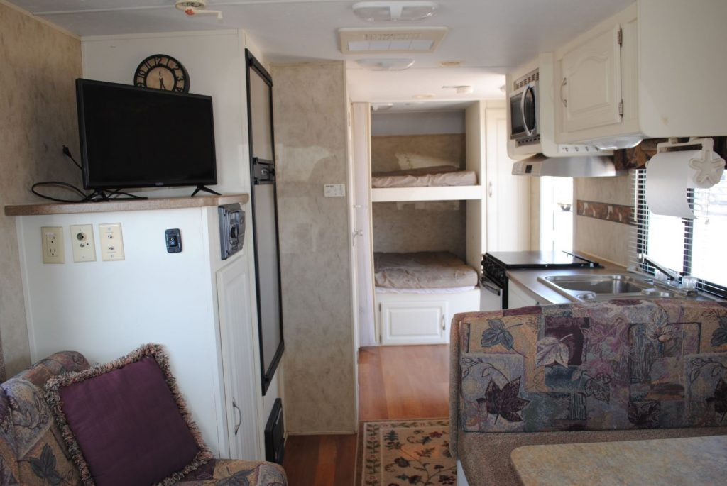 Long view of kitchen. Bunk bed sleeping area.
