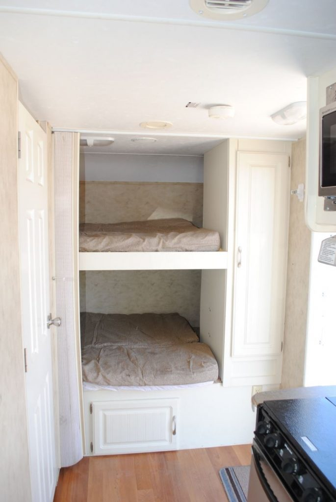 Close up of bunk bed sleeping area. Cabinet storage.