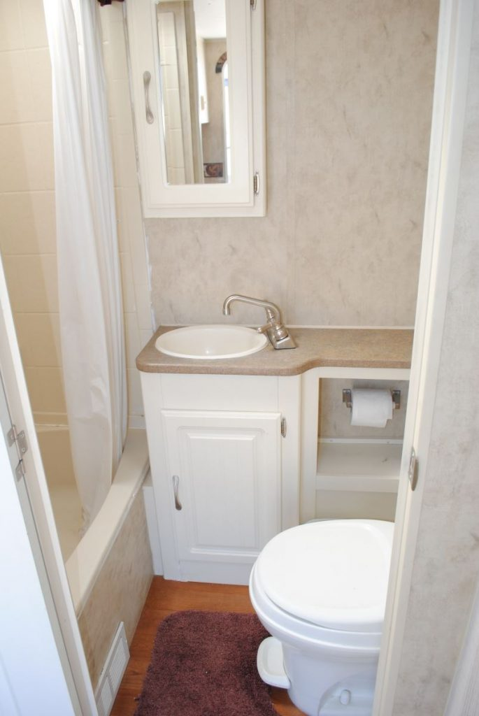 Bathroom sink, tub shower and toilet. Medicine cabinet with mirror and cabinet storage.