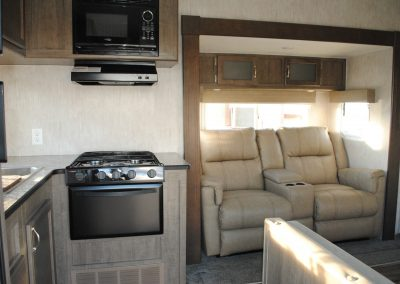Stove, stove hood, microwave. Two seater sofa with middle storage and drink holder. Overhead storage and windows.