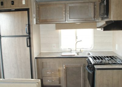 Refrigerator, sink, window, storage cabinets, stove, stove hood and microwave. Partial bench and table. Veneer flooring.