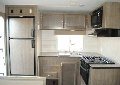 Refrigerator, sink and window, storage cabinets, stove, microwave and counter top.