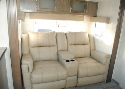 Close up of two seater sofa and windows. Middle console storage and drink holders.