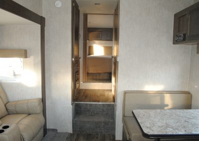 Looking through open door to bedroom. Partial view of sofa and bench seat with table. Storage cabinets.