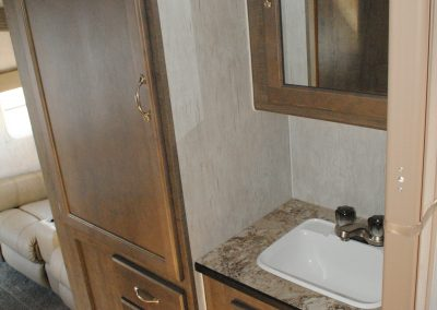 Bathroom sink, cabinet with mirror, storage cabinets and drawers.