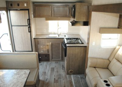 Refrigerator, sink with window, stove, cabinets for storage, partial view of bench seat and table, partial view of sofa.