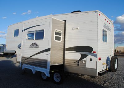 Exterior left side of 5th wheel, side slide extended, three windows. Partial view of rear with one window.