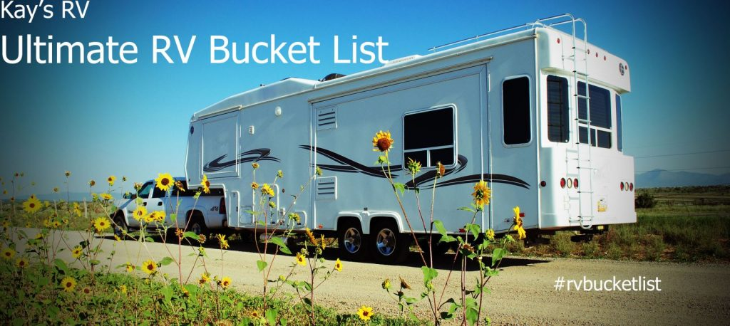 Pick up with hitched fifth wheel camper on dirt road with sunflowers and New Mexico blue sky above.